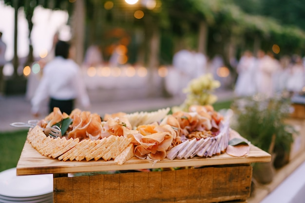 Деревянная доска с сыром и ветчиной прошутто на свадебном мероприятии на открытом воздухе