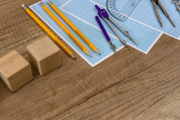 Деревянная доска с чертежными инструментами и миллиметровой бумагой