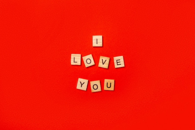 Wooden plaque with the text i love you on a red background. composition valentine's day. banner. flat lay, top view.