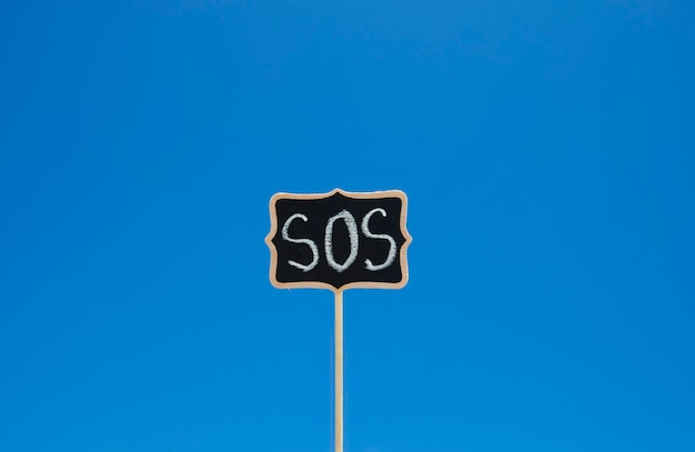 Wooden plaque with the word sos