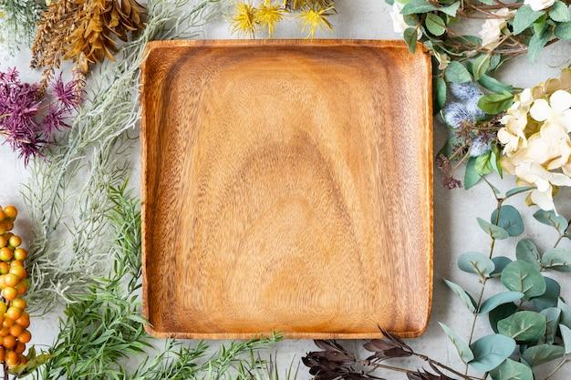 Деревянная тарелка и ботанические орнаменты на мраморном столе
