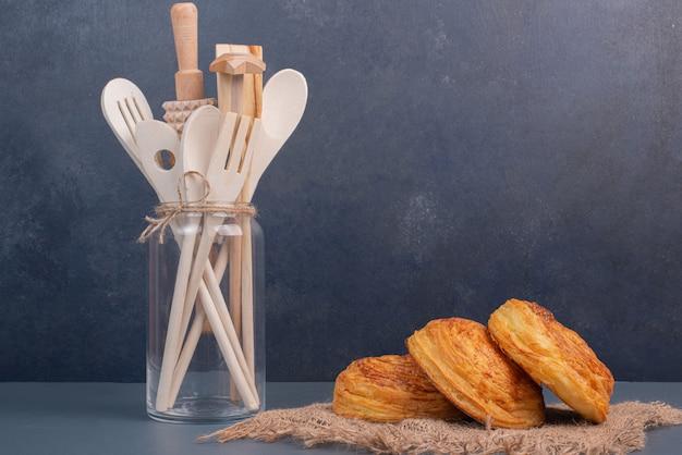 Piatto di legno del forno con utensili da cucina sulla parete di marmo.