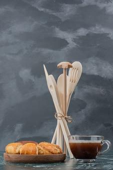 Piatto di legno di panetteria con utensili da cucina su marmo.