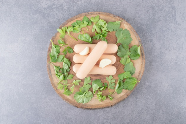 A wooden plate of boiled sausages with parsley and garlics