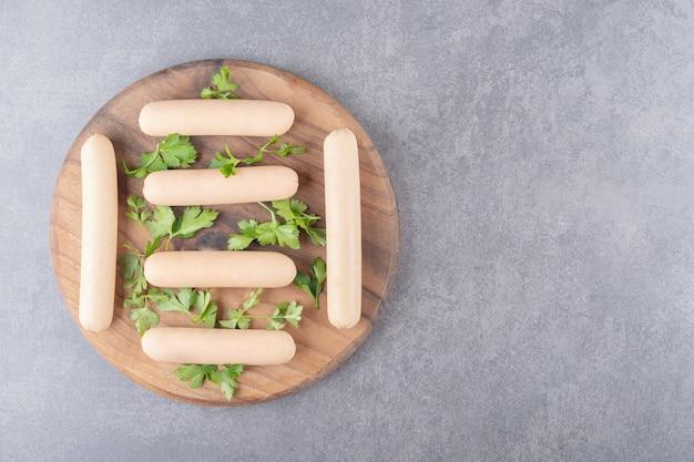 Un piatto di legno di salsicce bollite con prezzemolo
