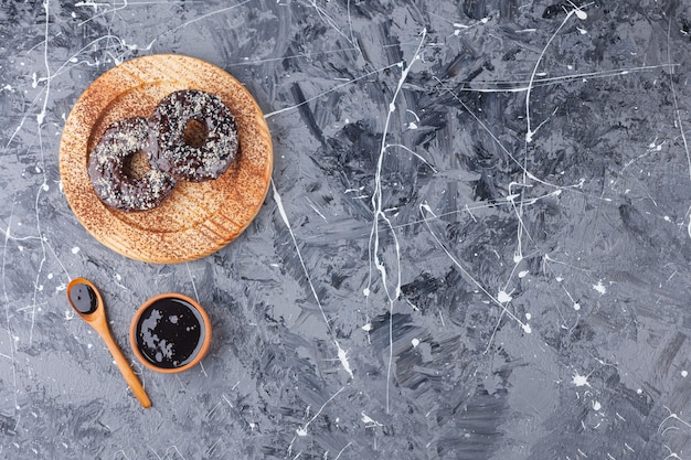 Wooden plate of chocolate donuts with coconut sprinkles on marble background.