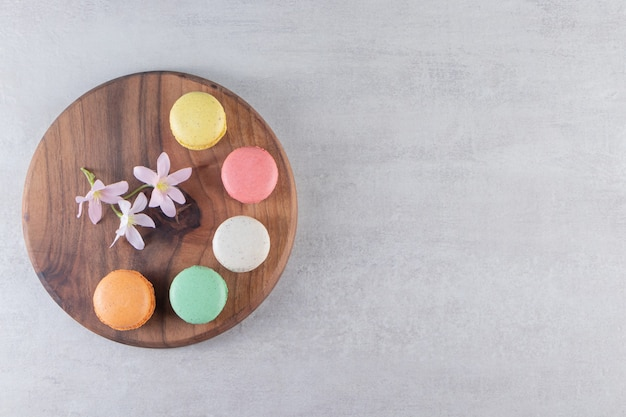 Wooden plate of colorful sweet macaroons with flowers on stone background.