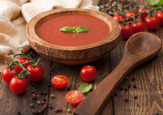 Wooden plate of creamy tomato soup with wooden spoon, pepper and kitchen cloth on wooden board. with raw tomatoes.
