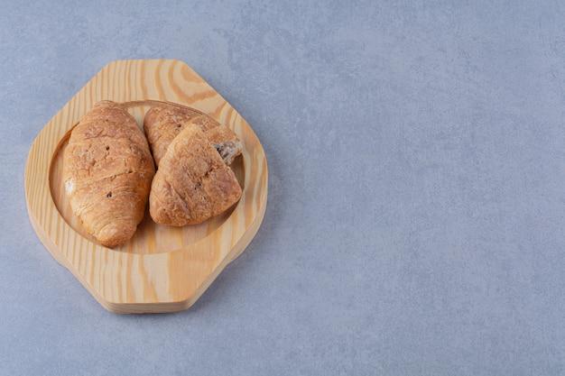 Un piatto di legno di croissant con delizioso cioccolato.