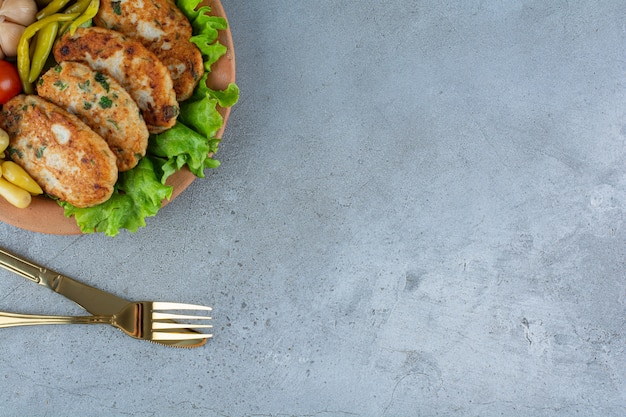 Wooden plate of delicious chicken cutlets on marble surface.