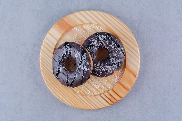 Un piatto di legno di deliziose ciambelle al cioccolato con codette