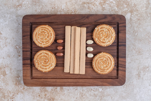 Wooden plate of delicious crunchy biscuits on marble surface.