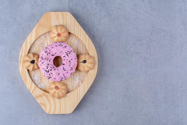 Un piatto di legno di deliziosa ciambella rosa con biscotto dolce.