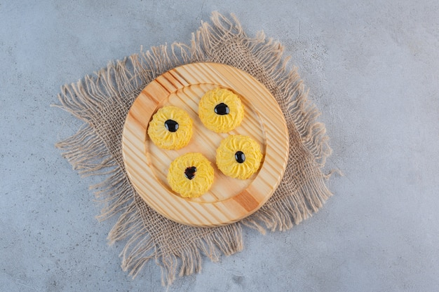 A wooden plate of delicious round biscuit on stone.