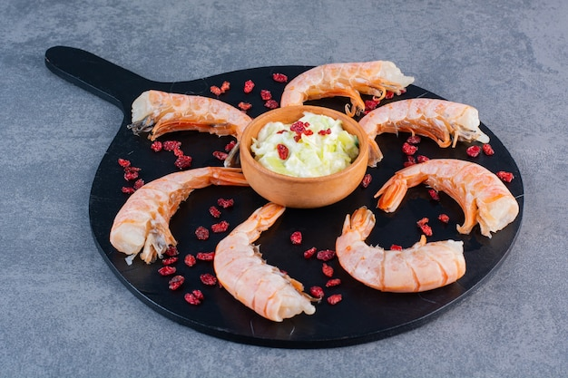 A wooden plate of delicious shrimps on a stone background.