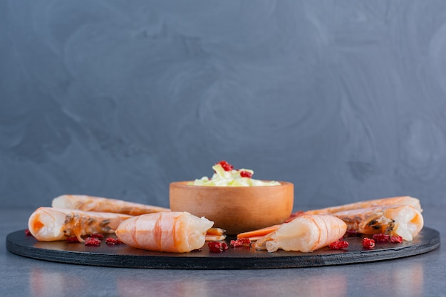 A wooden plate of delicious shrimps on a stone surface