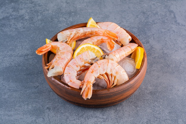 A wooden plate of delicious shrimps with ice cubes and sliced lemon on a stone background.