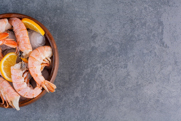 Un piatto di legno di deliziosi gamberetti con cubetti di ghiaccio e fette di limone su uno sfondo di pietra.