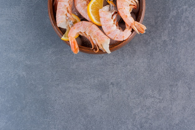 A wooden plate of delicious shrimps with ice cubes and sliced lemon on a stone surface