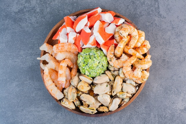 A wooden plate of delicious shrimps with tasty crab sticks on a stone surface