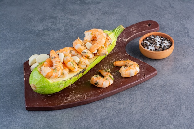 A wooden plate of delicious shrimps with zucchini and garlic on a stone background.