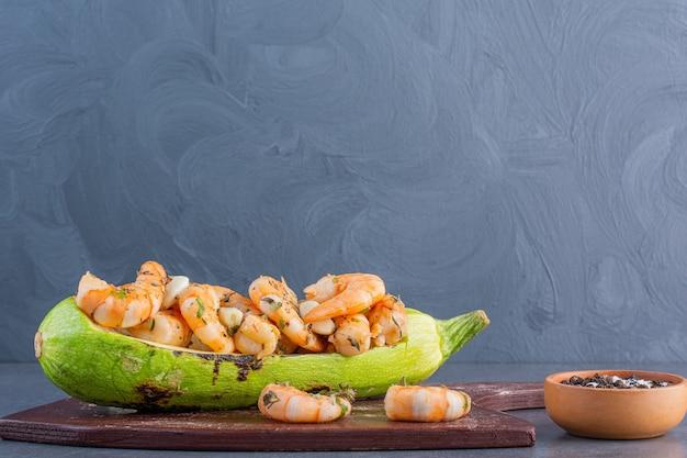 Un piatto di legno di deliziosi gamberetti con zucchine e aglio su uno sfondo di pietra.