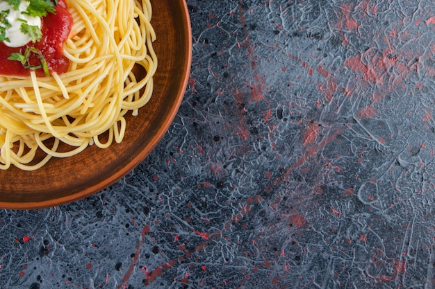Wooden plate of delicious spaghetti with tomato sauce on marble surface.