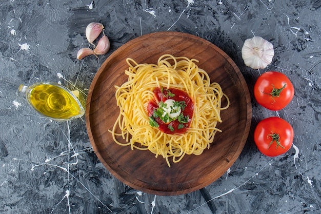 Wooden plate of delicious spaghetti with tomato sauce and vegetables on marble surface.
