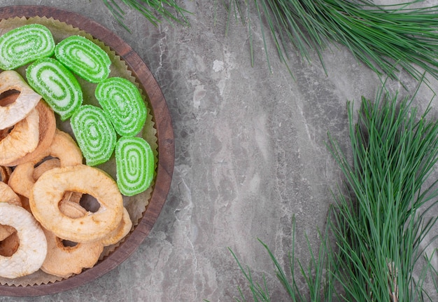 Wooden plate of dried apple rings and green marmalade candies on marble surface.