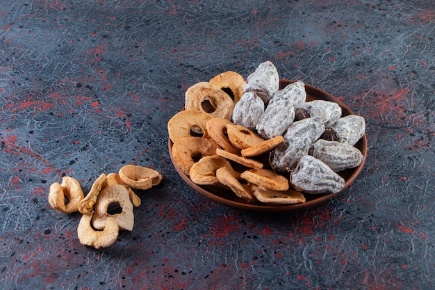Wooden plate of dried apple rings and persimmons on dark surface.