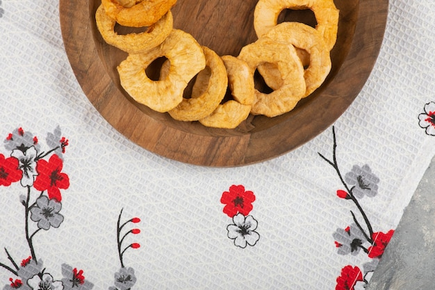Wooden plate of dried apple rings placed on white tablecloth.