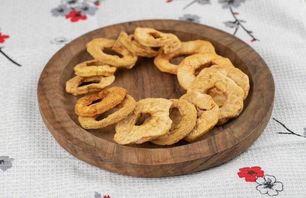 Wooden plate of dried apple rings on white tablecloth.