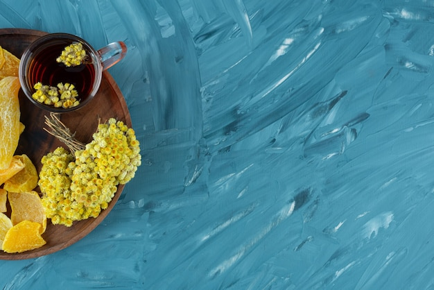 Piatto di legno di frutta secca e bicchiere di tè su sfondo blu.