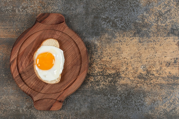 A wooden plate of egg on the white bread slice.