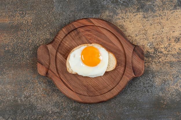 Un piatto di legno di uova sulla fetta di pane bianco.