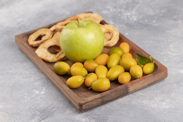 Wooden plate of fresh cumquats, apple and dried apple rings on marble.