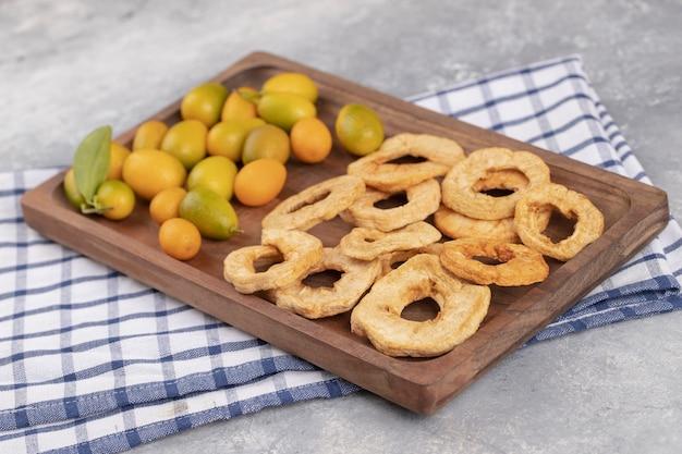 Piatto di legno di cumquat freschi e anelli di mela essiccati su fondo di marmo.