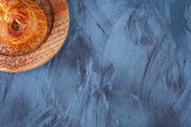 Piatto di legno di pasticceria fresca fragrante su marmo.