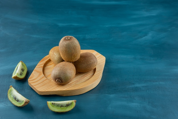 Wooden plate of fresh kiwi fruits on marble surface.