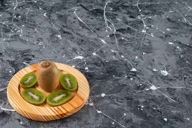 Wooden plate of fresh kiwi slices on marble background.