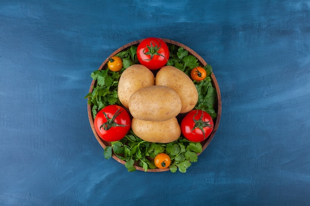 Wooden plate of fresh potato and tomatoes on blue surface.
