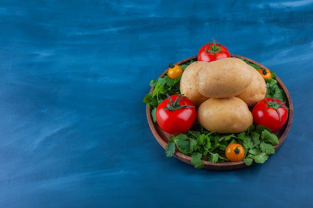 Wooden plate of fresh potato and tomatoes on blue table.