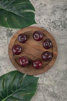 Un piatto di legno di prugne viola fresche con foglie verdi.