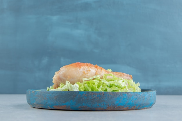 Un piatto di legno di carne di coscia di pollo fritto con lattuga a fette.
