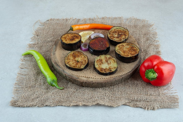 Un piatto di legno di melanzane a fette fritte con peperoni sul tavolo di marmo.