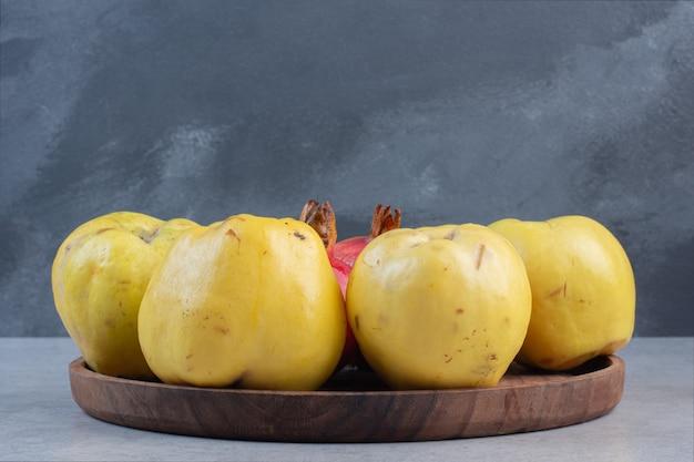 Piatto di legno pieno di mele cotogne su sfondo grigio.