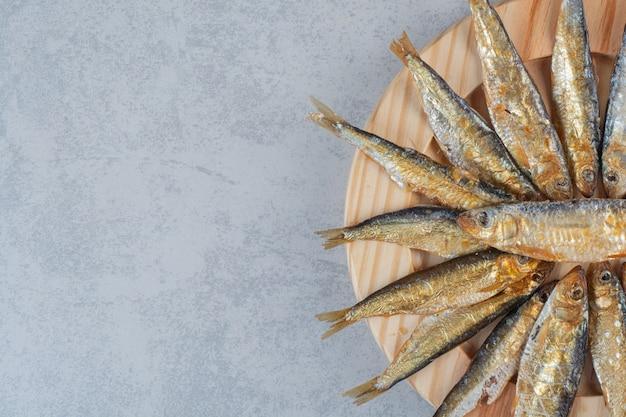 Un piatto di legno pieno di pesce delizioso.