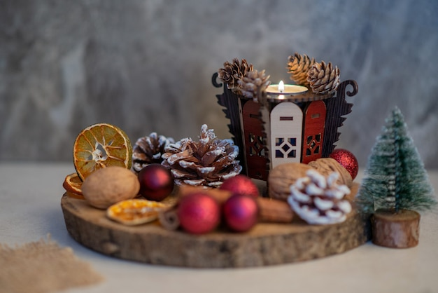 Un piatto di legno pieno di arance secche e palline rosse di natale. foto di alta qualità