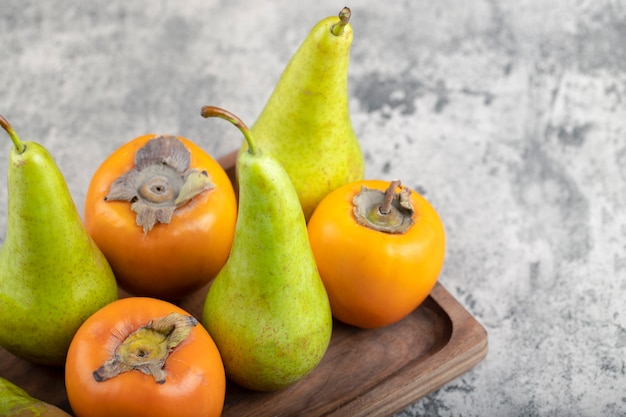 Wooden plate full of green pears and persimmon on stone.