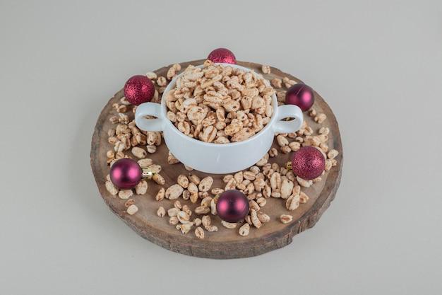Un piatto di legno pieno di cereali sani con le palle di natale.